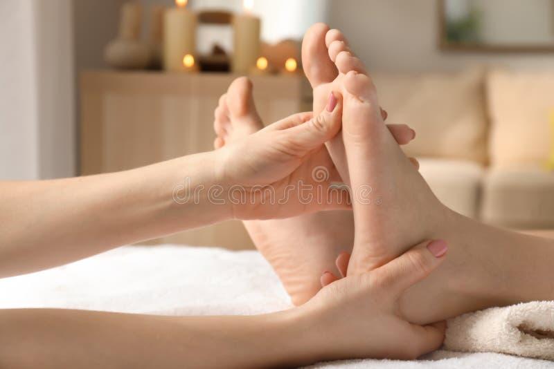 Mujer joven hermosa que recibe masaje del pie en salón del balneario imágenes de archivo libres de regalías