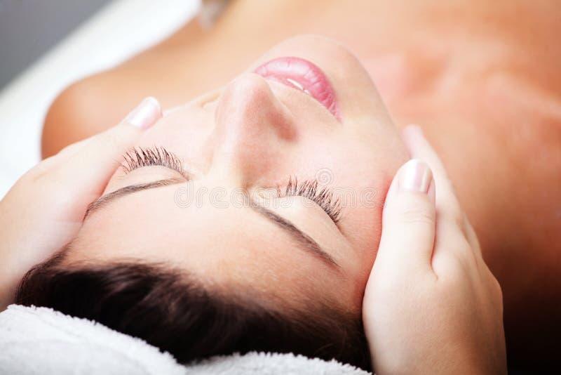 Mujer joven hermosa que recibe masaje facial. imagen de archivo
