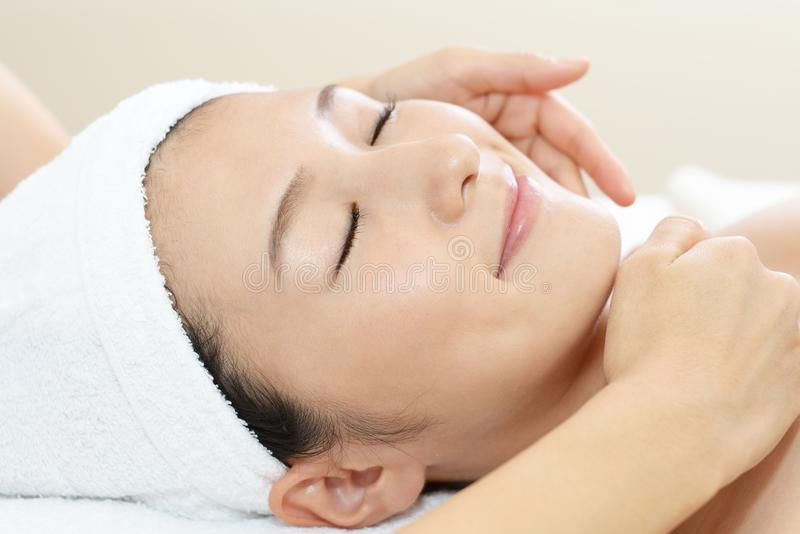 Mujer joven hermosa que recibe masaje facial fotos de archivo libres de regalías