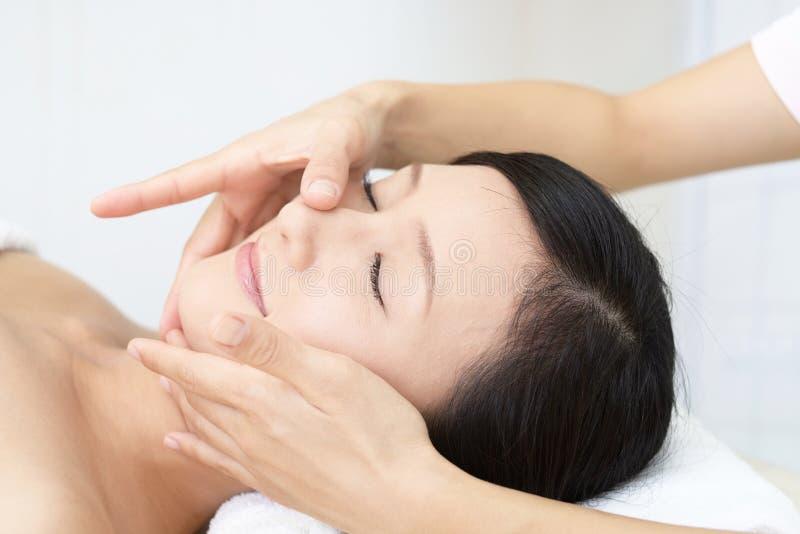 Mujer joven hermosa que recibe masaje facial imágenes de archivo libres de regalías