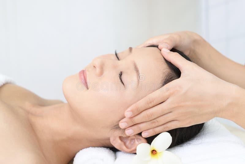 Mujer joven hermosa que recibe masaje facial foto de archivo