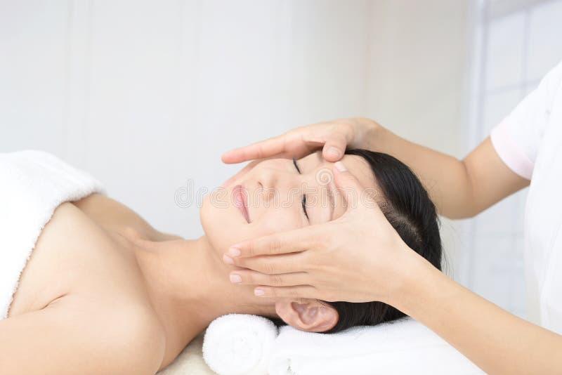 Mujer joven hermosa que recibe masaje facial imagenes de archivo