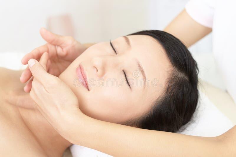 Mujer joven hermosa que recibe masaje facial fotos de archivo