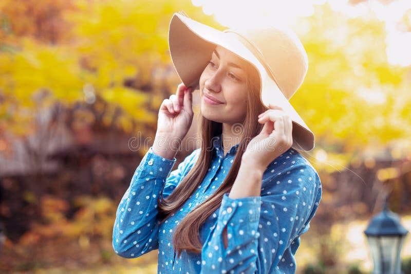 Mujer joven hermosa que recorre en parque del oto?o Mujer joven magnífica en caída con el sombrero grande, sonriendo y disfrutand fotografía de archivo