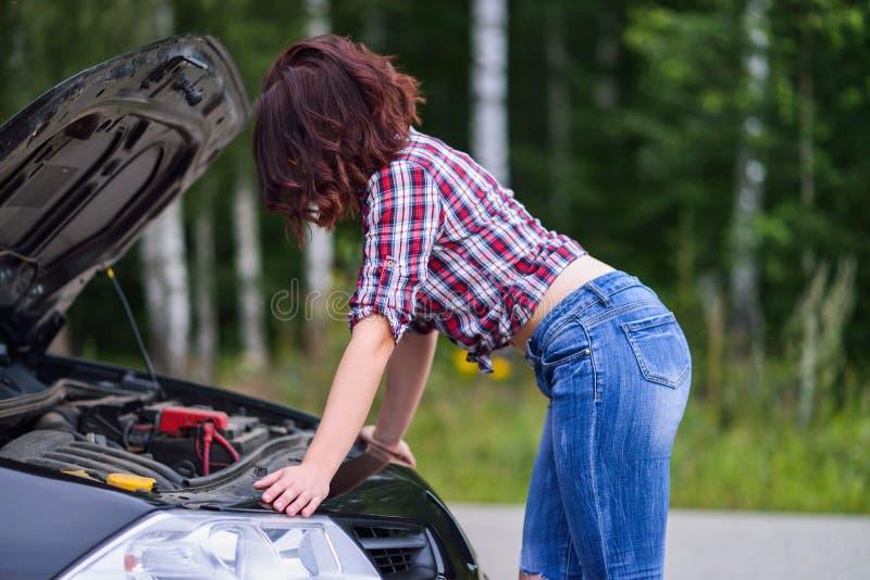 Mujer joven hermosa que repara su coche quebrado cerca del camino imagenes de archivo