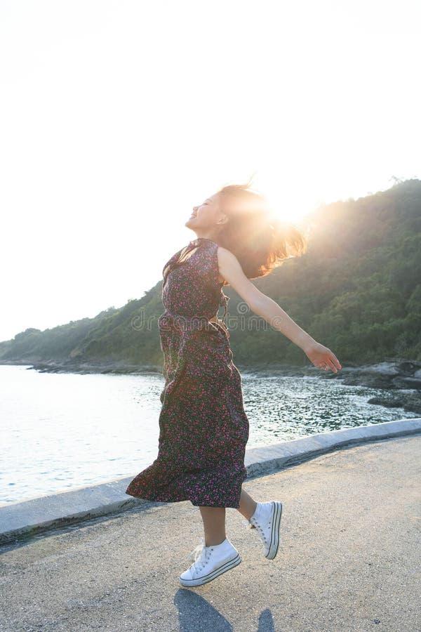 Mujer joven hermosa que salta en el lado de mar contra el sol que se enciende sobre el cielo imágenes de archivo libres de regalías