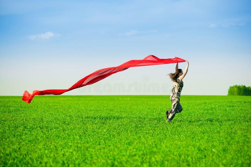 Mujer joven hermosa que salta en un prado verde imágenes de archivo libres de regalías