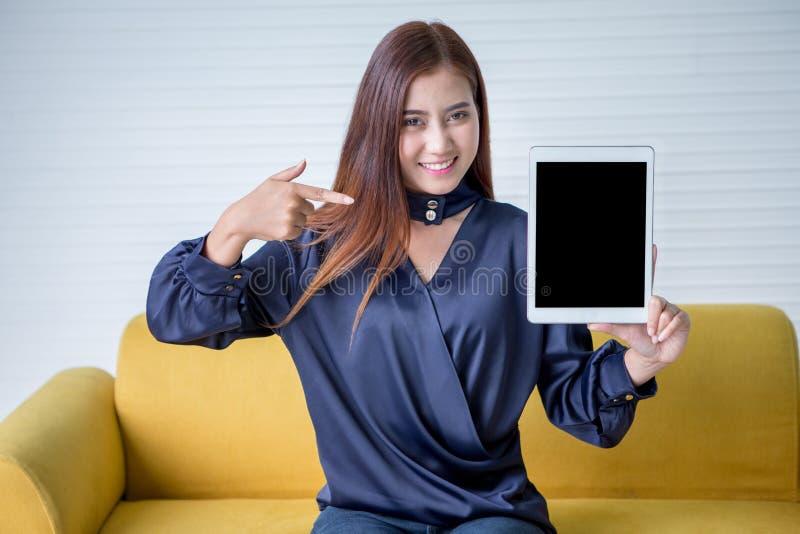 Mujer joven hermosa que señala el finger y que muestra la tableta digital aislada en fondo del tablero blanco Muchacha sonriente  fotos de archivo libres de regalías