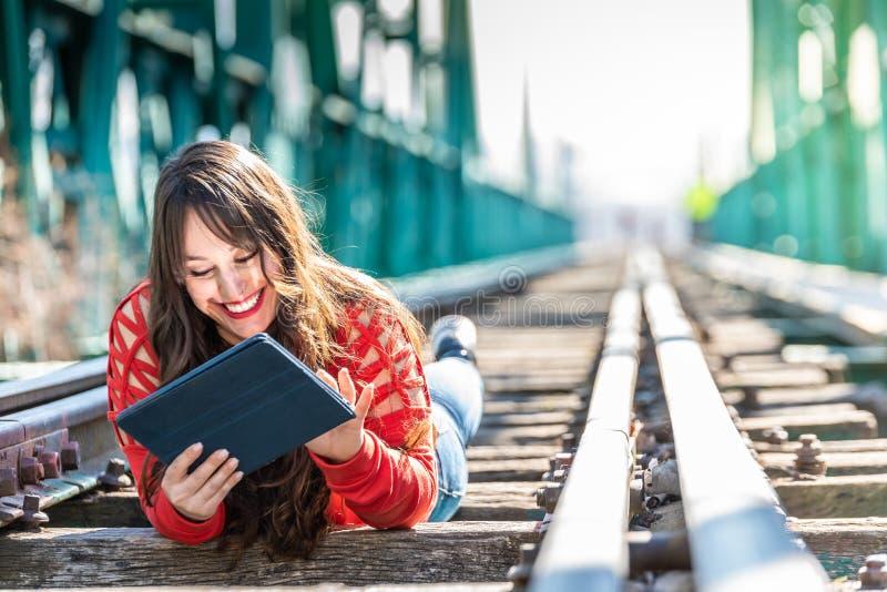 Mujer joven hermosa que se acuesta en v?as del tren usando la tableta de Digitaces fotos de archivo libres de regalías