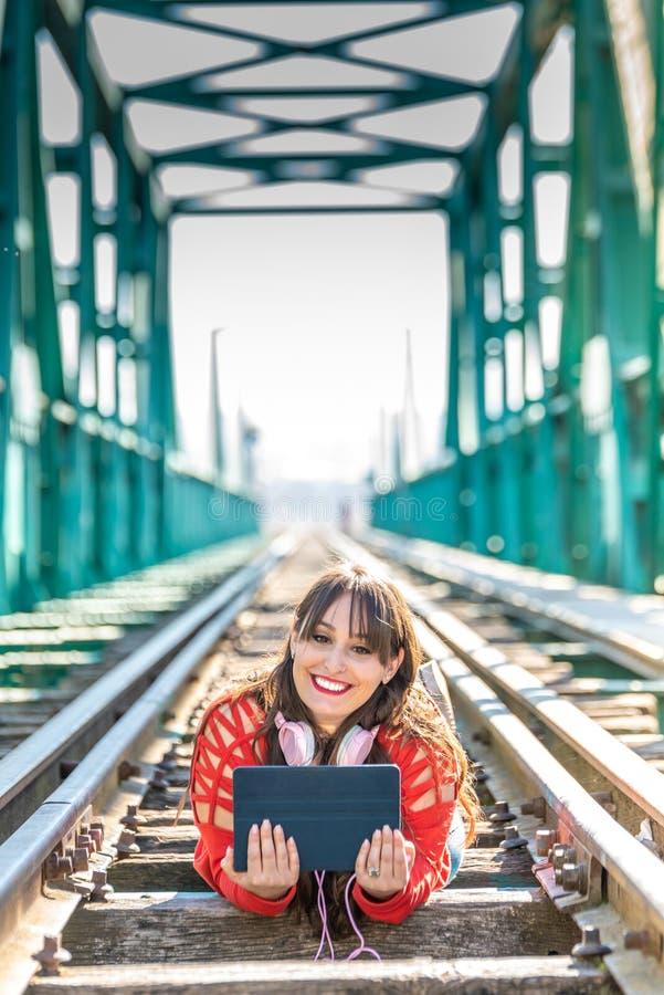 Mujer joven hermosa que se acuesta en v?as del tren usando la tableta de Digitaces fotografía de archivo
