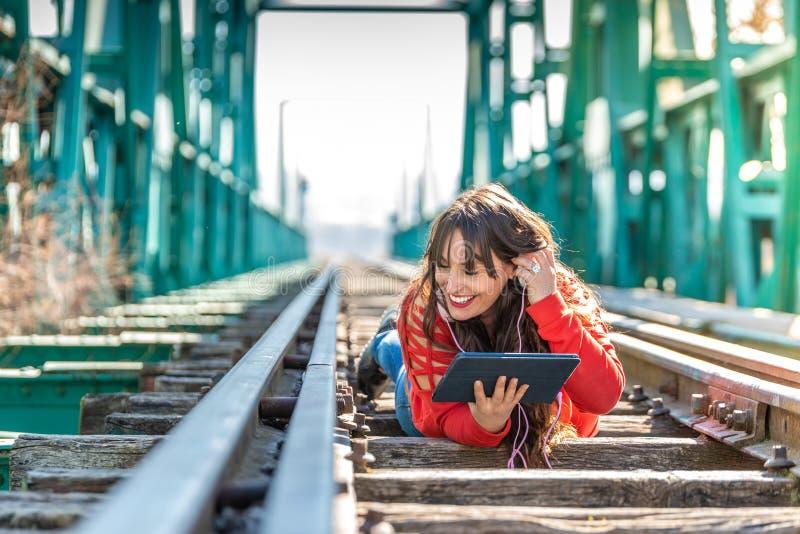 Mujer joven hermosa que se acuesta en v?as del tren usando la tableta de Digitaces imagen de archivo libre de regalías
