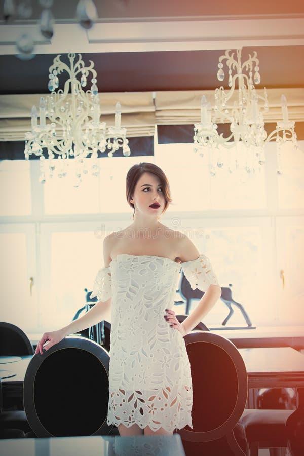 Mujer joven hermosa que se coloca cerca de la tabla en el cuarto de lujo fotos de archivo