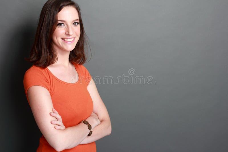 Mujer joven hermosa que se coloca con los brazos cruzados foto de archivo