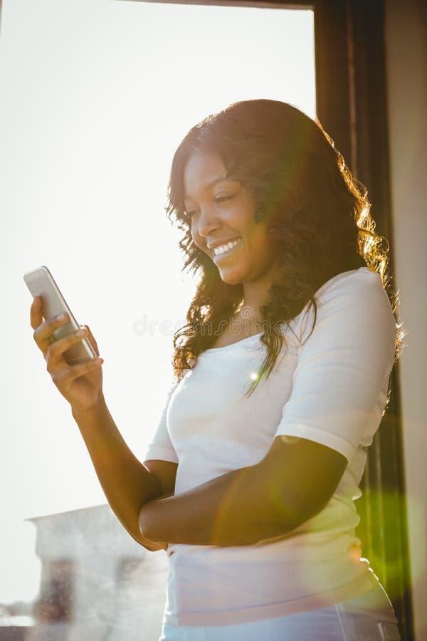 Mujer joven hermosa que se coloca delante de una ventana foto de archivo