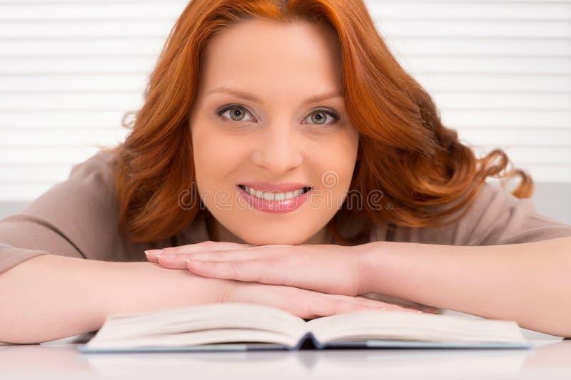 Mujer joven hermosa que se inclina en el libro fotografía de archivo
