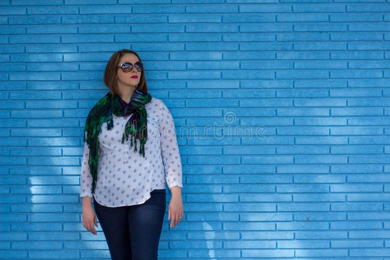 Mujer joven hermosa que se opone a una pared de ladrillo azul fotografía de archivo