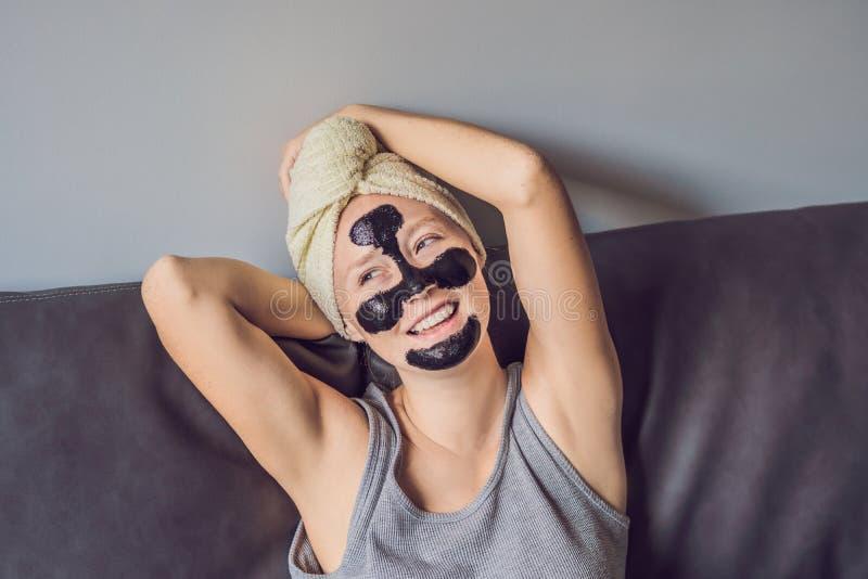 Mujer joven hermosa que se relaja con la mascarilla en casa Mujer alegre feliz que aplica la máscara negra en cara fotos de archivo