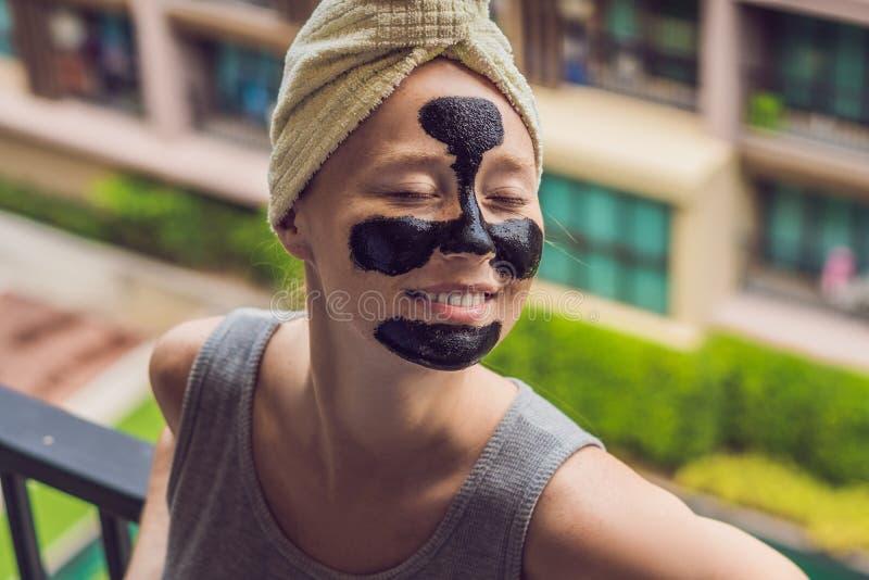 Mujer joven hermosa que se relaja con la mascarilla en casa Mujer alegre feliz que aplica la máscara negra en cara fotos de archivo libres de regalías