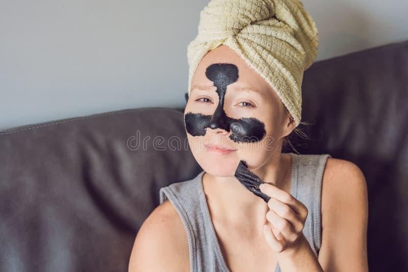 Mujer joven hermosa que se relaja con la mascarilla en casa Mujer alegre feliz que aplica la máscara negra en cara foto de archivo libre de regalías