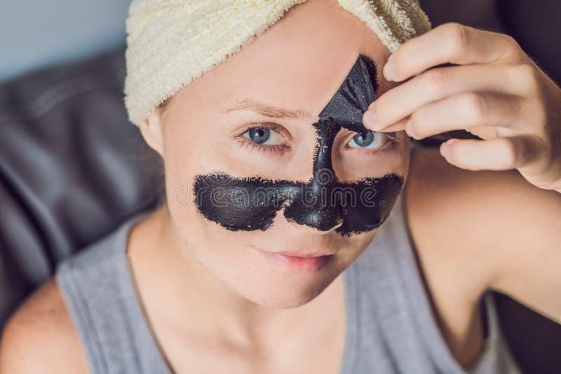 Mujer joven hermosa que se relaja con la mascarilla en casa Mujer alegre feliz que aplica la máscara negra en cara fotografía de archivo