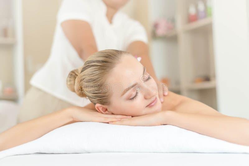 Mujer joven hermosa que se relaja con masaje de la mano en el balneario de la belleza Masaje del cuerpo Cerrado para arriba de la fotografía de archivo libre de regalías