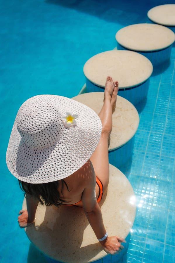 Mujer joven hermosa que se relaja en la piscina foto de archivo libre de regalías