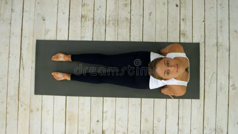 Mujer joven hermosa que se resuelve dentro, haciendo ejercicio de la yoga en el cuarto, actitud boca abajo del perro, mukha del a fotos de archivo