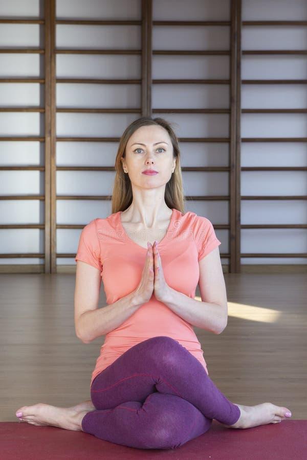 Mujer joven hermosa que se resuelve en el interior del desván, haciendo ejercicio de la yoga en la estera azul, ejercicio de la b foto de archivo libre de regalías