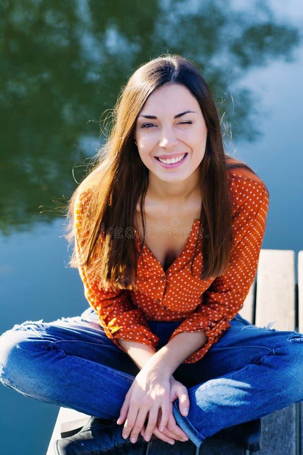 Mujer joven hermosa que se sienta al borde del embarcadero de madera imagen de archivo