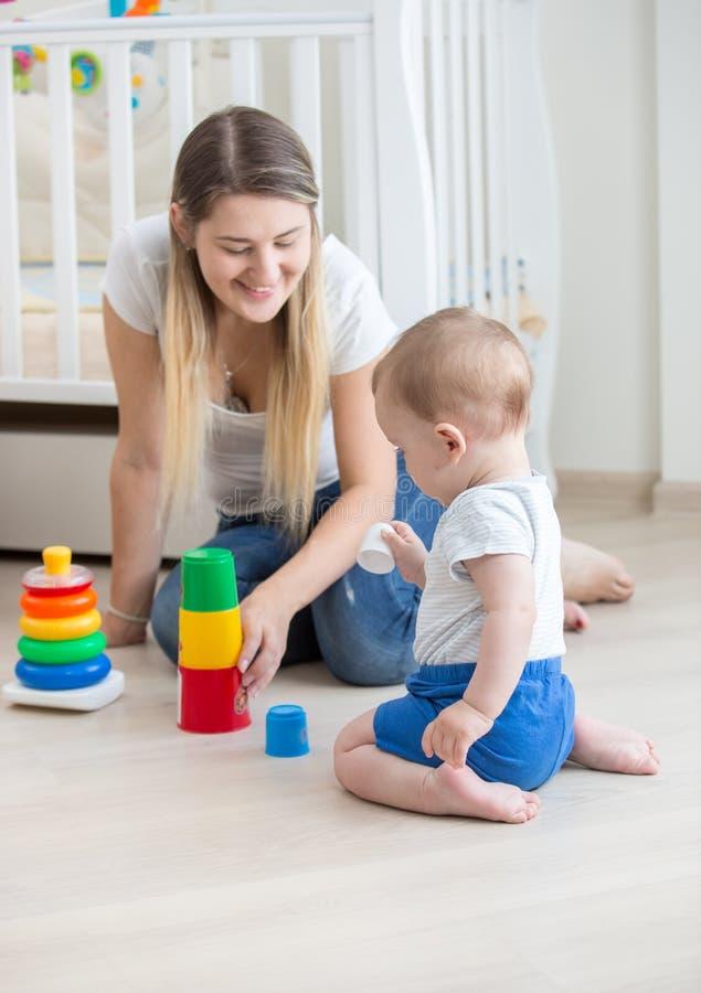 Mujer joven hermosa que se sienta con sus 10 meses del hijo y que juega con los juguetes fotografía de archivo