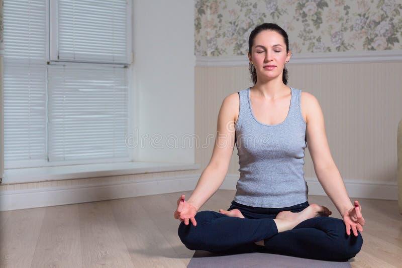 mujer joven hermosa que se sienta en actitud del loto y que medita en casa fotografía de archivo libre de regalías