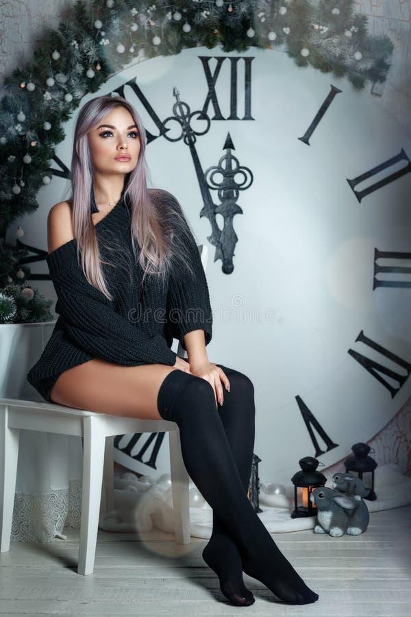 Mujer joven hermosa que se sienta en el fondo de una decoración grande de la Navidad del reloj, sosteniendo una linterna, esperan imágenes de archivo libres de regalías