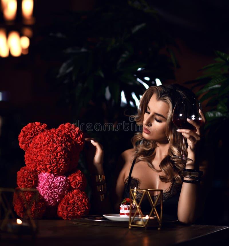 Mujer joven hermosa que se sienta en el restaurante que celebra cumpleaños con la torta y el oso rosado del actual regalo de las  imagen de archivo