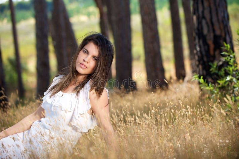 Mujer joven hermosa que se sienta en hierba en el campo foto de archivo