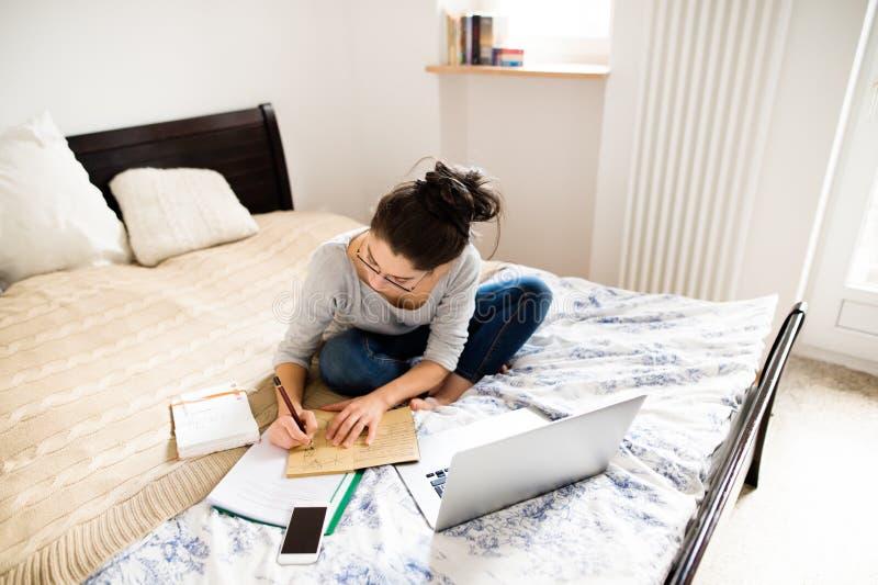 Mujer joven hermosa que se sienta en la cama, trabajando Ministerio del Interior fotos de archivo