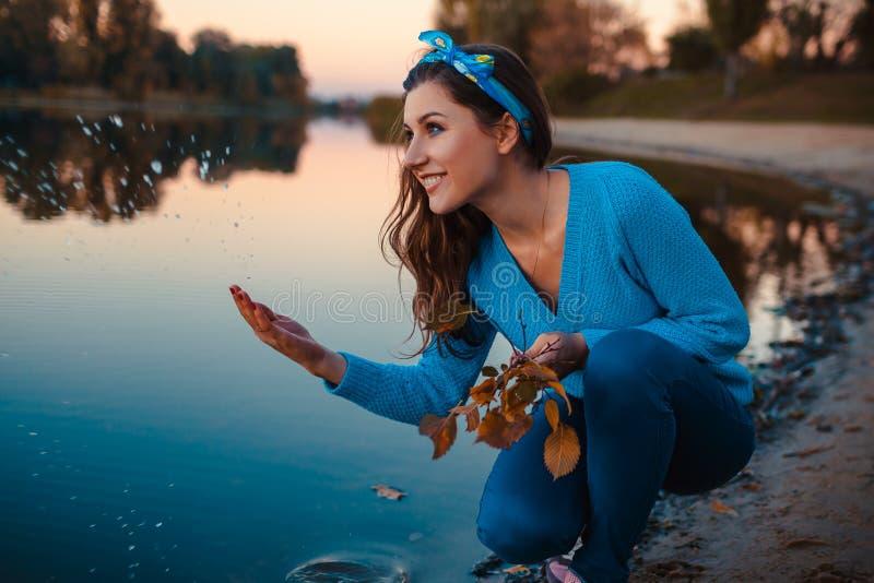 Mujer joven hermosa que se sienta en la orilla del río del otoño que salpica el agua y que lleva a cabo ramas fotografía de archivo
