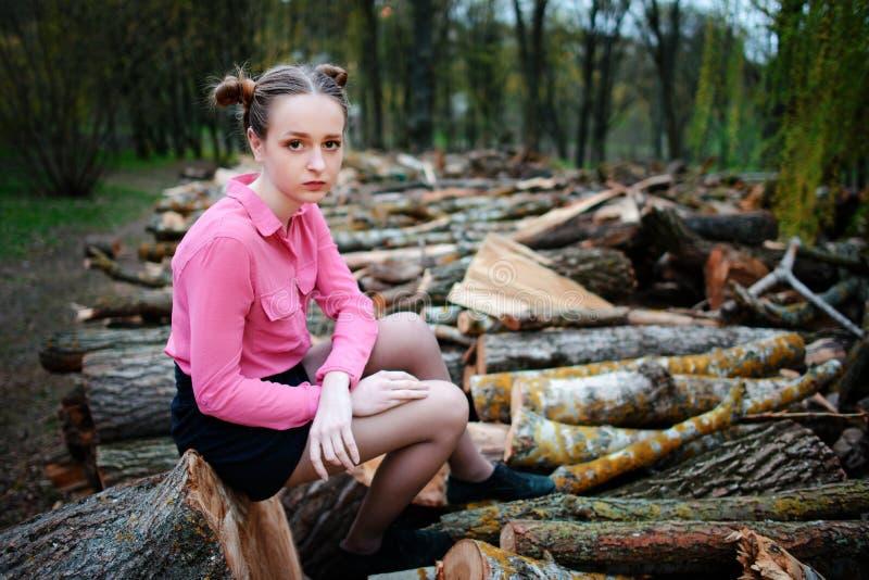 Mujer joven hermosa que se sienta en la pila de troncos de árbol derribados en el bosque imágenes de archivo libres de regalías