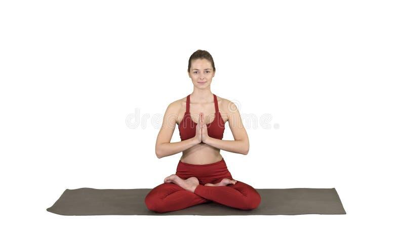 Mujer joven hermosa que se sienta en la posición cambiante de Lotus de la actitud de la yoga de sus manos respecto al fondo blanc imagenes de archivo