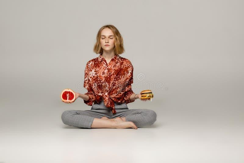Mujer joven hermosa que se sienta en la posición y meditar de la yoga fotografía de archivo