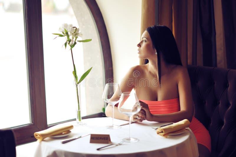 Mujer joven hermosa que se sienta en la tabla solamente en un restaurante fotografía de archivo