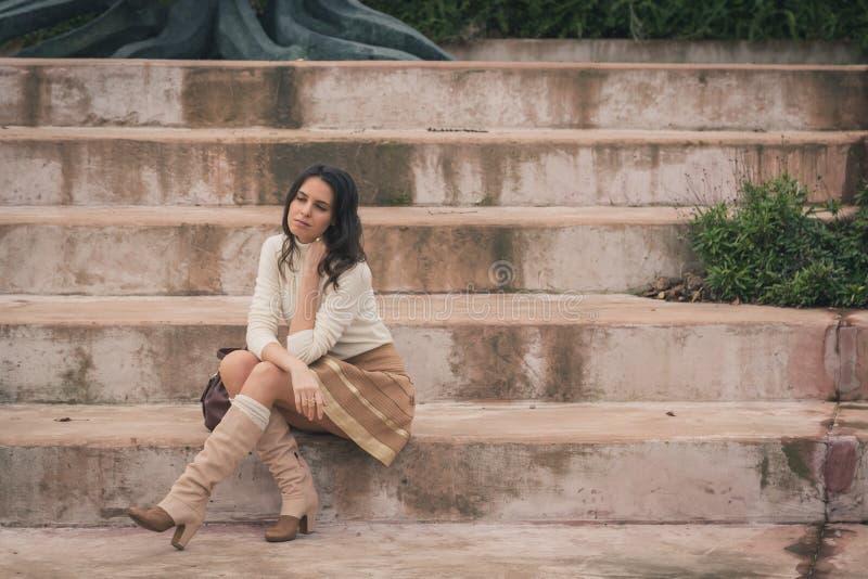 Mujer joven hermosa que se sienta en pasos concretos foto de archivo libre de regalías
