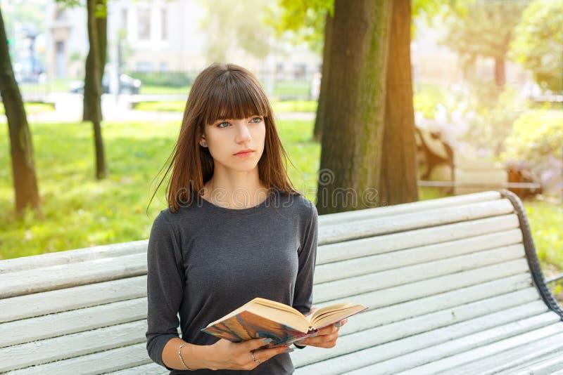 Mujer joven hermosa que se sienta en un banco en la calle que lee un libro fotografía de archivo libre de regalías