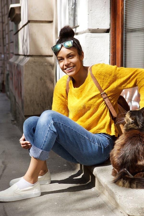 Mujer joven hermosa que se sienta por una calle con el gato imagenes de archivo