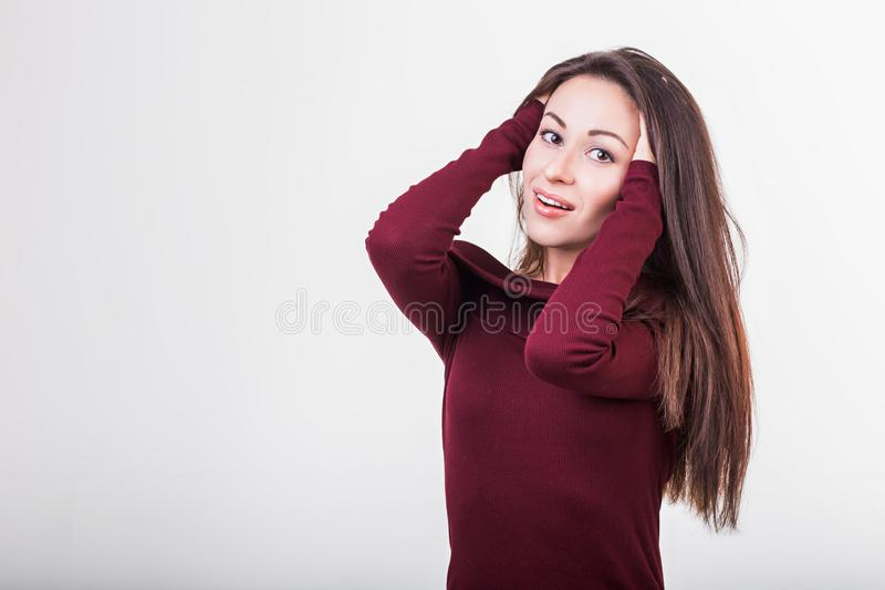 Mujer joven hermosa que se sostiene el pelo sano y brillante, blanco del estudio fotografía de archivo