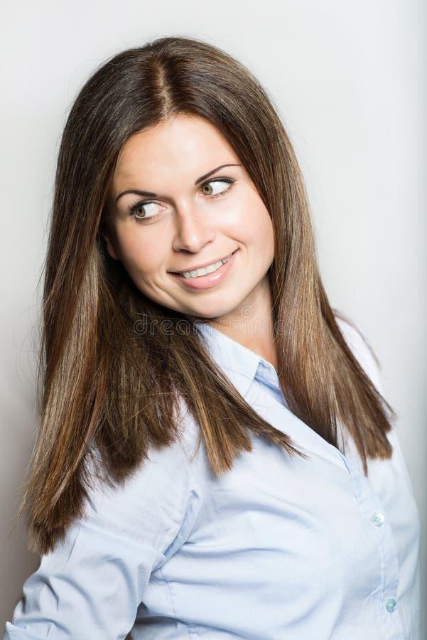 Mujer joven hermosa que sonríe en el fondo blanco fotografía de archivo