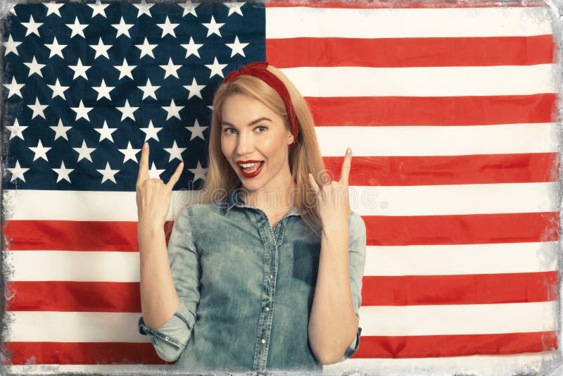Mujer joven hermosa que sonríe y que gesticula contra el contexto de la bandera americana el Día de la Independencia fotografía de archivo