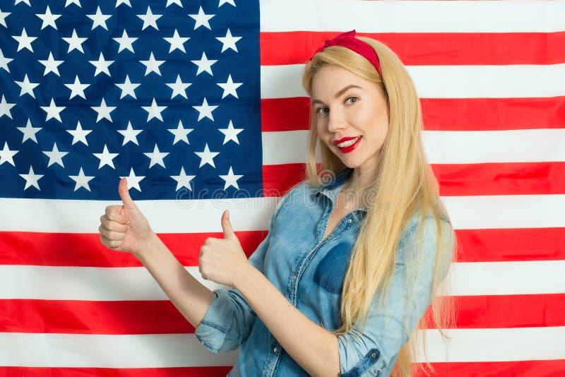Mujer joven hermosa que sonríe y que gesticula contra el contexto de la bandera americana el Día de la Independencia imágenes de archivo libres de regalías