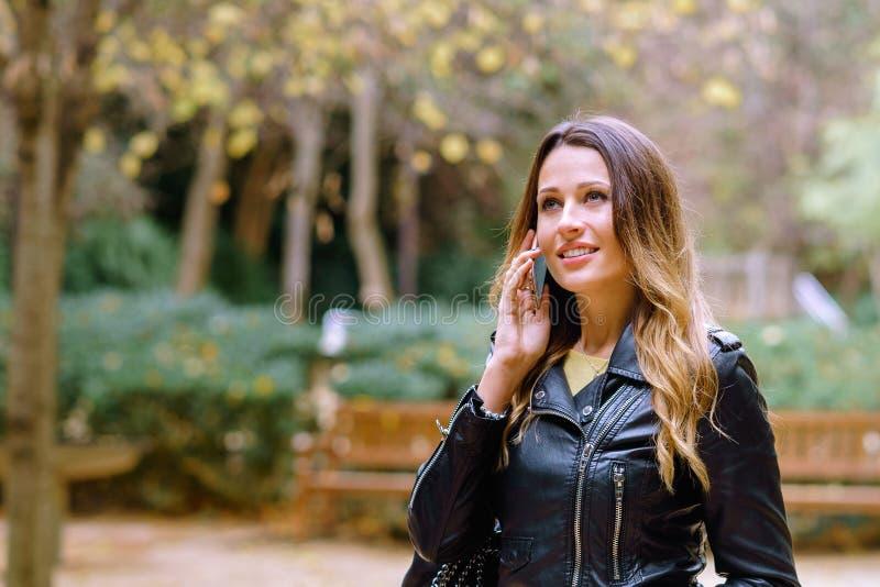 Mujer joven hermosa que sonríe y que mira lejos y que habla en smartphone foto de archivo