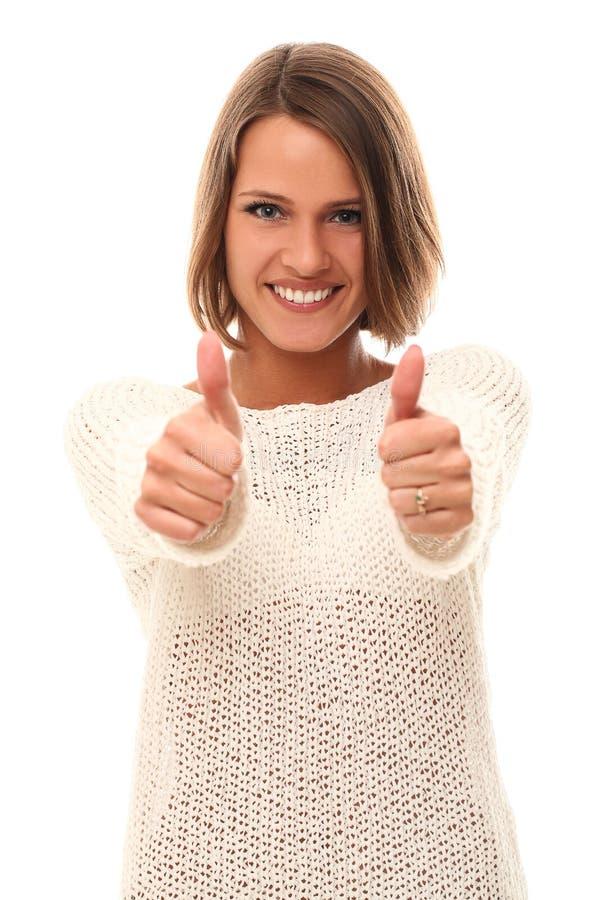 Mujer joven hermosa que sonríe y que muestra los pulgares para arriba fotografía de archivo