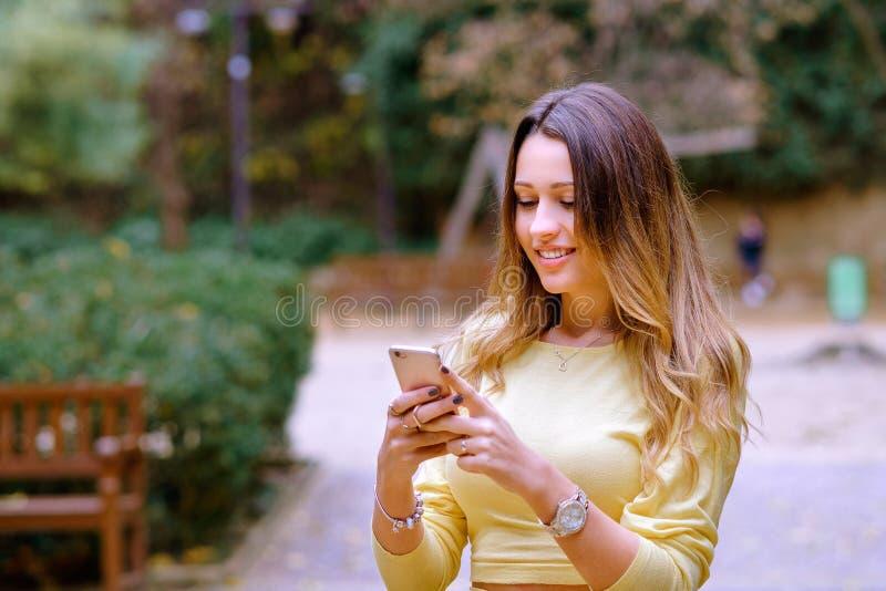 Mujer joven hermosa que sonríe y smartphone de la ojeada fotografía de archivo